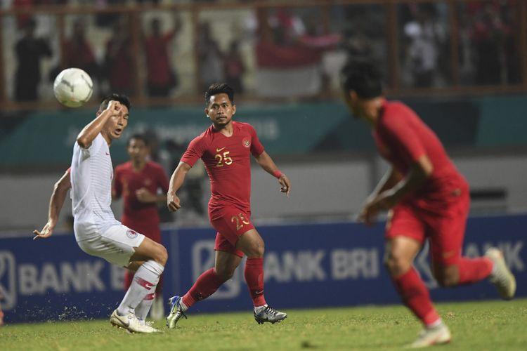 Pesepak bola Timnas Indonesia Andik Vermansah (tengah) mengumpan bola ke rekannya Irfan Jaya (kanan) saat melewati pesepak bola Timnas Hong Kong Yang Huang (kiri) dalam laga International Friendly Match di Stadion Wibawa Mukti, Cikarang, Bekasi, Jawa Barat, Selasa (16/10/2018). Pertandingan tersebut berakhir imbang dengan skor 1 - 1. ANTARA FOTO/Hafidz Mubarak A/wsj.