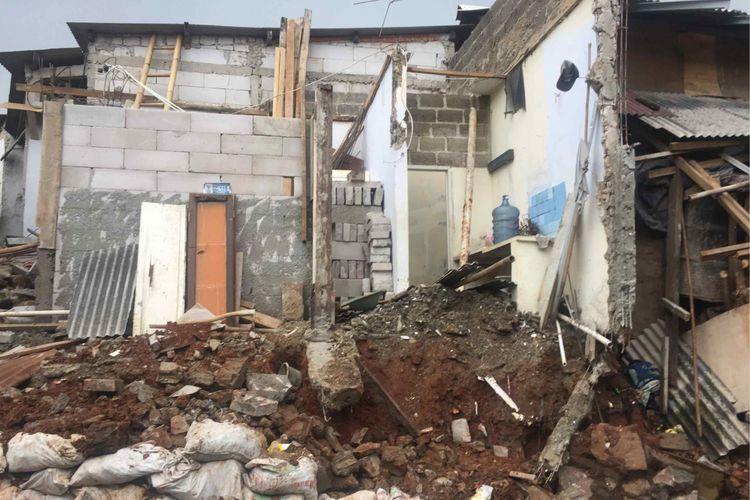 Dua rumah di RT 006 RW 001 Kelurahan Bambu Apus, Pamulang, Tangerang Selatan ditimpa sebuah rumah yang ambrol karena hujan deras yang terjadi di wilayah tersebut, Rabu (7/11/2018) malam. Pantauan Kompas.com, tampak sejumlah bagian dua rumah tersebut mengalami kerusakan setelah ditimpa beton bangunan dari rumah berada lebih tinggi dari dua rumah sebelumnya. Rumah yang ambrol berada di RT 006 RW 004 yang berlokasi di samping kedua rumah tersebut, Kamis (8/11/2018).