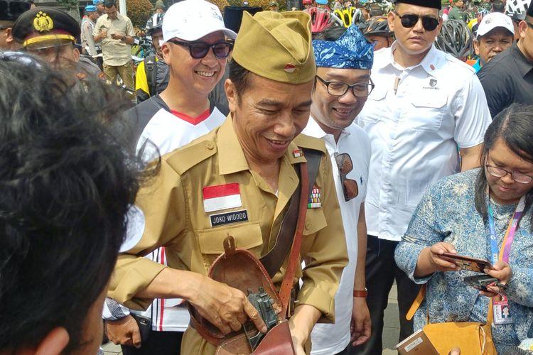 Presiden Joko Widodo mengenakan pakaian ala Bung Tomo saat bersepeda di depan Gedung Sate yang juga kantor Gubernur Jawa Barat, Sabtu (10/11/2018) pagi. Jokowi lalu memamerkan pistol mainan yang disimpan ditasnya.
