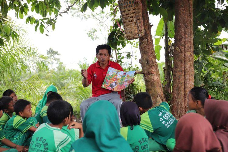 Yosep membacakan cerita kepada anak-anak di ladang sekolah, disela-sela waktu istirahat. Yosep merawat nasionalisme di pedalaman Kaltara dengan mendekatkan buku kepada anak.