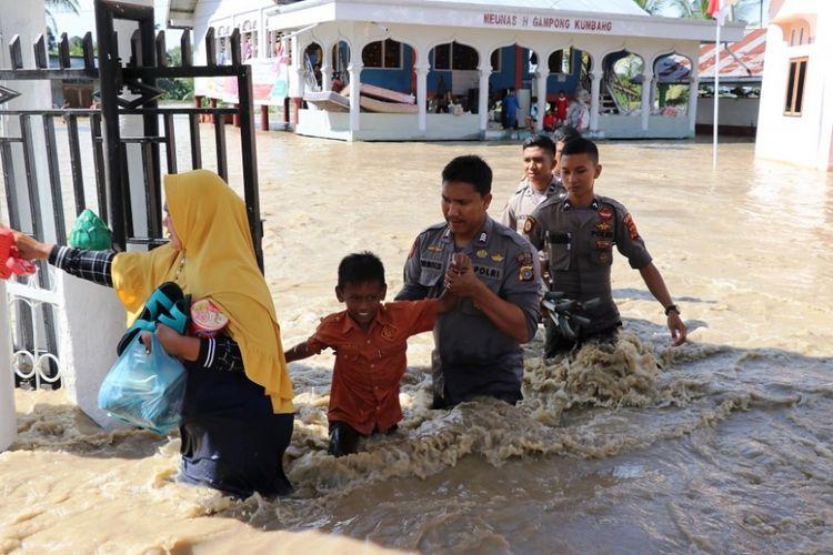 Polisi mengevakuasi korban banjir di Desa Mancang, Kecamatan Syamtalira Aron, Kabupaten Aceh Utara, MInggu (18/11/2018)