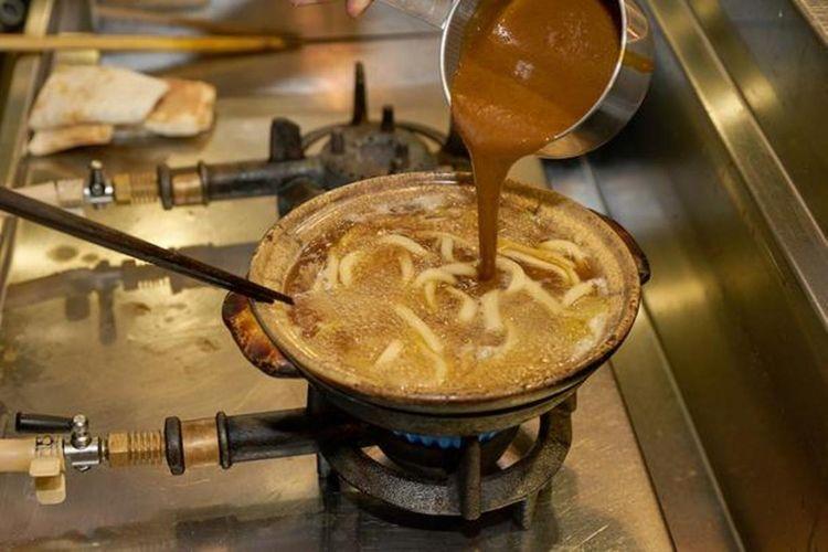 Kare yang kaya akan bumbu dimasukkan ke dalam rebusan kaldu yang mendidih.