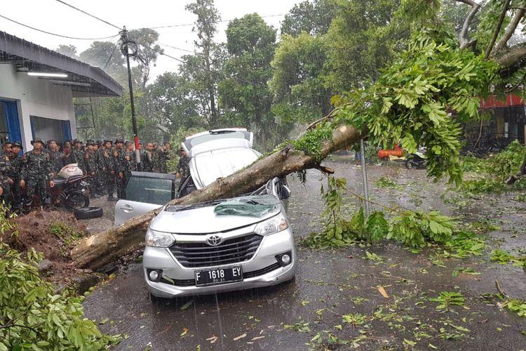 Angin puting beliung yang melanda wilayah selatan Kota Bogor, Jawa Barat, Kamis (6/12/2018) sekitar pukul 15.00 WIB, menyebabkan satu orang tewas karena mobilnya tertimpa pohon tumbang.