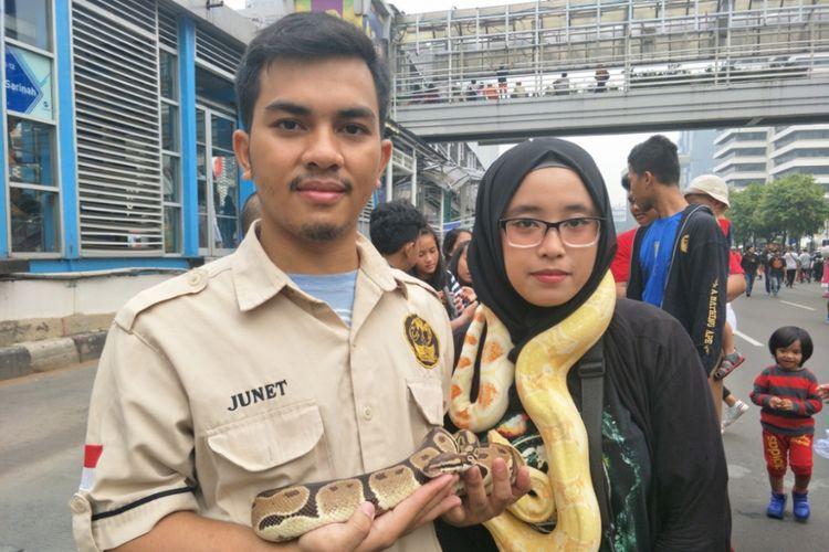 Ketua Room Pets Djakarta (RPD) Ilham (kiri) dan anggota RPD Sari (kananpl) memamerkan reptil peliharaannya di Jalan MH Thamrin, Jakarta Pusat, Minggu (9/12/2018).