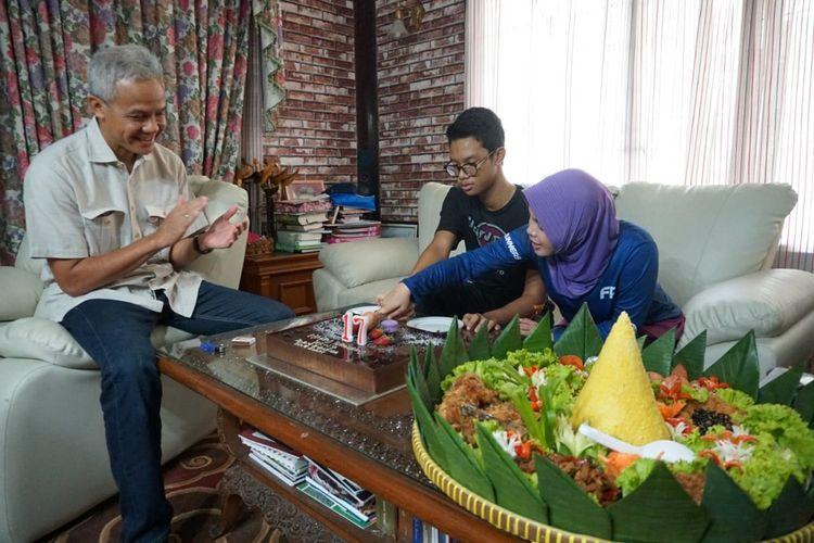 Gubernur Jawa Tengah Ganjar Pranowo (kiri) melewati hari kerja yang agak berbeda pada Jumat (14/12/2017) ini. Anak semata wayang Ganjar, Muhammad Zinedine Alam Ganjar (tengah) genap berusia 17 tahun. Suasana bahagia di tengah keluarga Gubernur Jateng itu dibagikan melalui akun Instagram @ganjar_pranowo. Dalam foto-foto yang diunggah Ganjar terlihat acara tiup lilin itu dirayakan  bersama ibunda Siti Atikoh.
