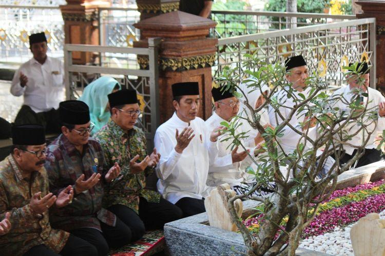 Presiden RI, Joko Widodo (Jokowi) bersama KH. Salahuddin Wahid (Gus Sholah), memanjatkan doa tawassul di pusara makam pendiri NU, KH. Hasyim Asyari, di Pesantren Tebuireng Jombang Jawa Timur, Selasa (18/12/2018).