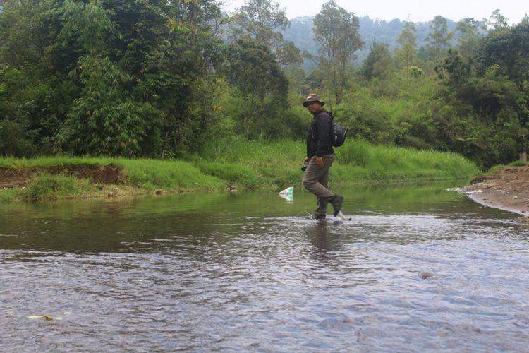 Salah satu pengunjung melintasi sungai saat menuju Air Terjun Coban Talun, Kota Batu, Minggu (6/1/2019)
