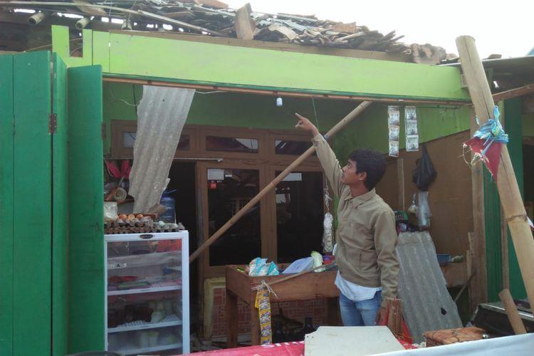 Seorang warga menunjukkn rumh yang rusak akibat diterjang puting beliung di Dusun Kopo Timur, Desa Muktijaya, Kecamatan Cilamaya Kulon, Kabupaten Karawang, Jumat (11/1/2019).