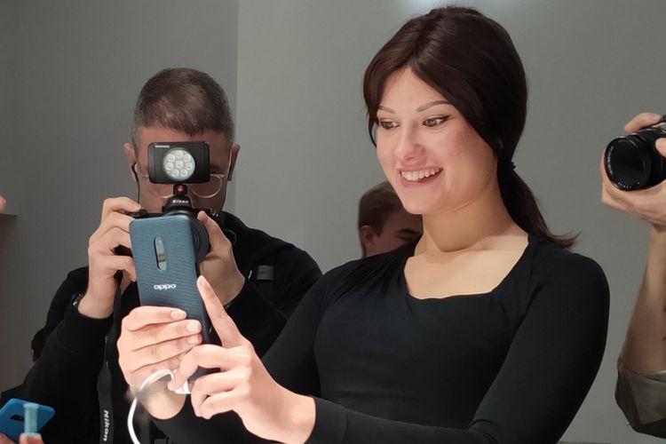 Model memeragakan ponsel Oppo dengan zoom optik 10x di ajang oppo Innovation Event di Barcelona, Spanyol, Sabtu (23/2/2019).