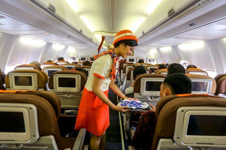 Awak kabin Garuda Indonesia, melayani penumpang pesawat dalam penerbangan Jakarta-Balikpapan, Jumat (7/12/2018). Garuda Indonesia meluncurkan layanan penerbangan bernuansa klasik bertajuk Garuda Indonesia Vintage Flight Experience dari tanggal 7-17 Desember 2018
