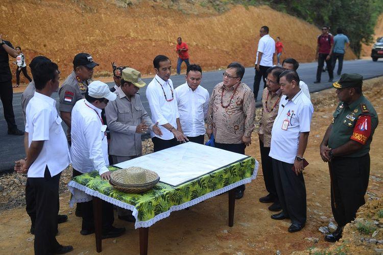 Presiden Joko Widodo (tengah) didampingi sejumlah pejabat terkait melihat peta kawasan salah satu lokasi calon ibu kota negara saat peninjauan di Gunung Mas, Kalimantan Tengah, Rabu (8/5/2019). ANTARA FOTO/Akbar Nugroho Gumay/foc.
