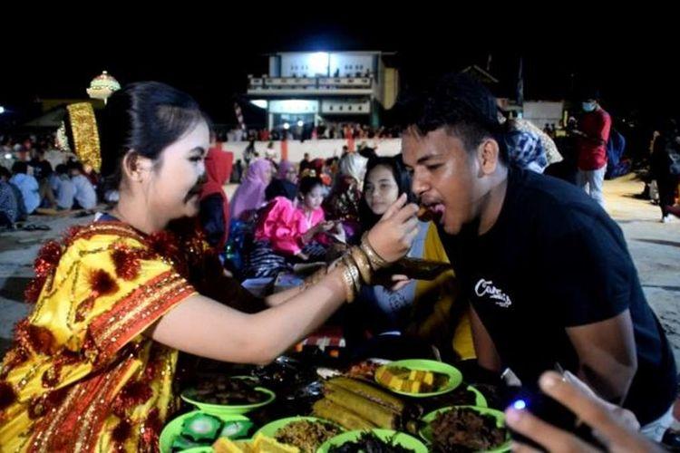 Seorang gadis yang mengenakan baju adat Buton, menyuapkan makanan kepada seorang tamu pria. Ini merupakan kegiatan tradisi kande tompa, atau tradisi mencari jodoh yang dilakukan masyarakat Kelurahan Tolandona, Kecamatan Sangia Wambulu, Kabupaten Buton Tengah, Sulawesi Tenggara