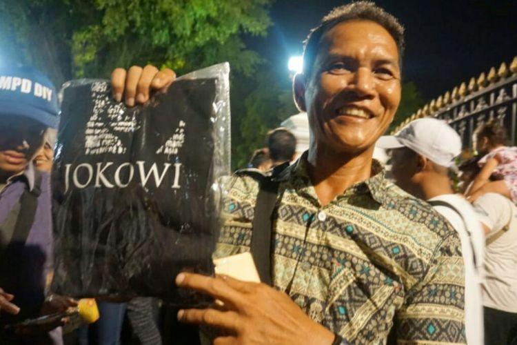 Andi Mugiono wisatawan asal Surabaya, Jawa Timur saat menunjukan kaos pemberian Presiden Joko Widodo