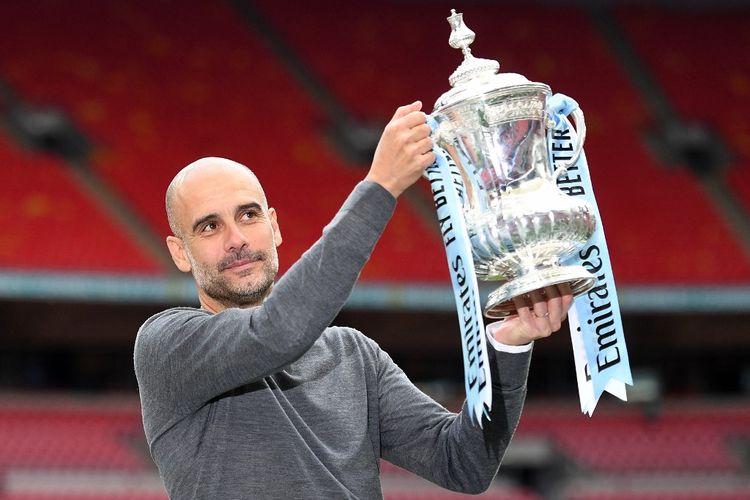 Manajer Manchester City, Pep Guardiola, mengangkat Piala FA usai laga final Man City Vs Watford di Stadion Wembley, London, Inggris, Sabtu (18/5/2019).