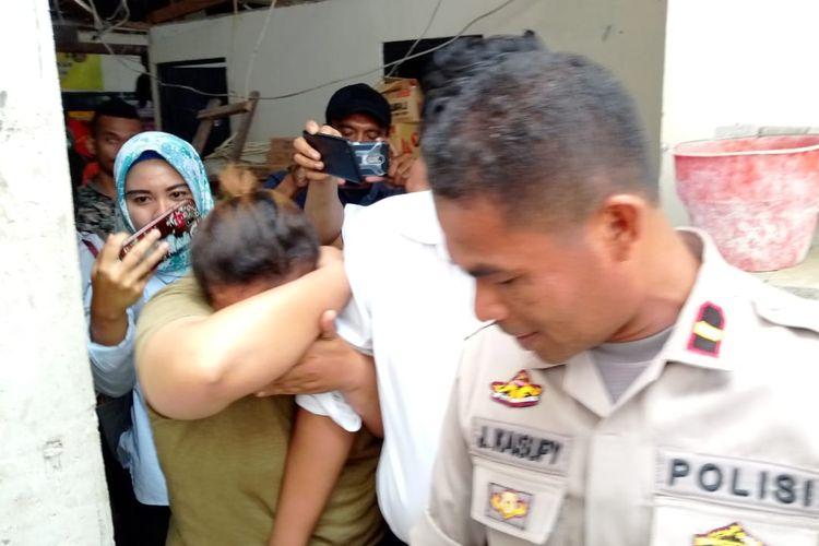 Sambil menutupi wajahnya, SH alias Ocah (25) digiring polisi ke sel tahanan Polres Pulau Ambon seusai menjalani pemeriksaan oleh penyidik unit PPA Satreskrim Polres Pulau Ambon, Rabu (10/4/2019)