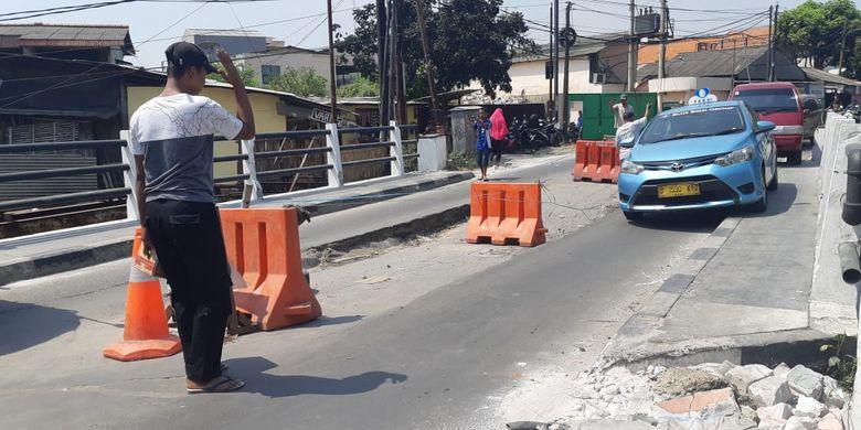 Seorang warga yang mengatur jalannya lalu lintas di jembatan yang amblas di kawasan Tegal Alur, Jakarta Barat, Selasa (23/7/2019).
