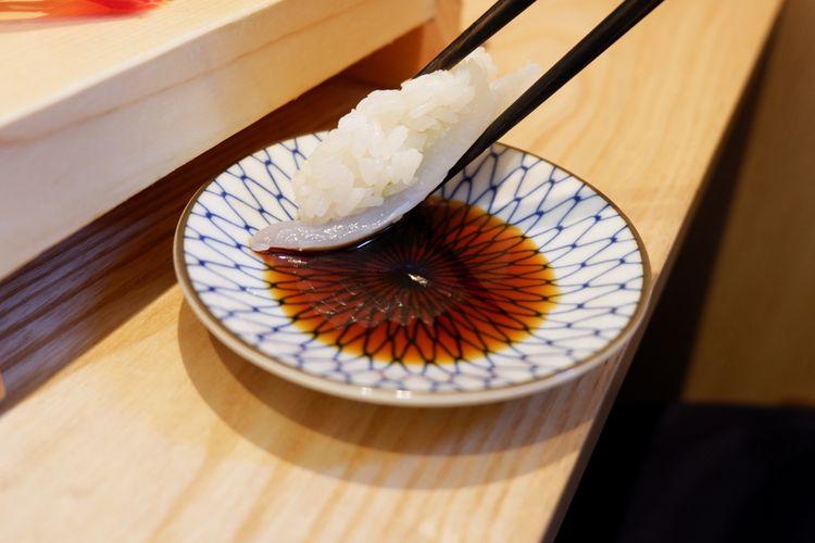 mencelup shari (nasi sushi) ke kecap asin