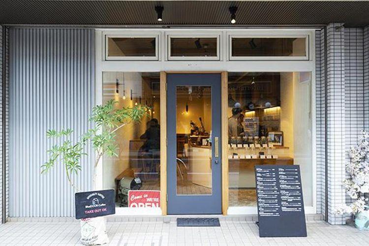 Area masuk kedai kopi memiliki pintu biru