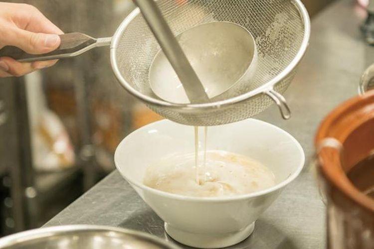 Busa putih di permukaan dari sup tulang babi, membuatnya terasa ringan