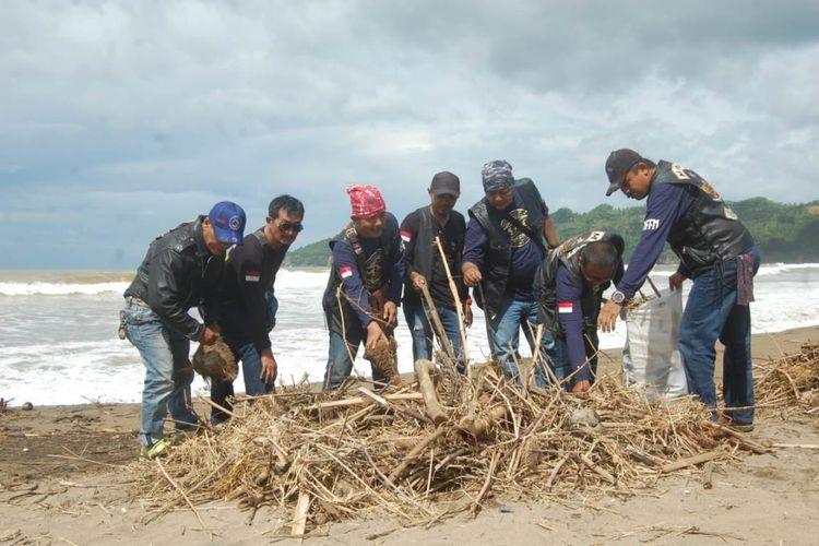 Para pemotor membersihkan sampah yang berada di pantai kili-kili lokasi konservasi penyu, kecamatan panggul kabupaten Trenggalek Jawa Timur (23/03/2019)