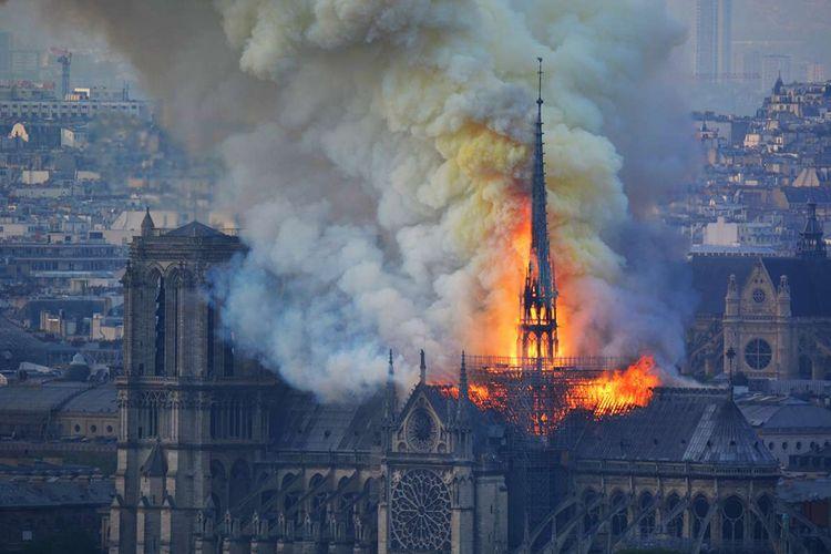 Api membakar bagian atas Gereja Notre Dame di Paris, Perancis, pada Senin (15/4/2019). Belum diketahui penyebab pasti kebakaran itu, api dengan cepat melalap atap dan puncak menara gereja bernuansa Gotik yang dibangun pada abad ke-12 itu.