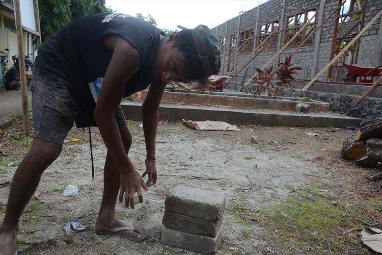 Rafid Marajabessy, putra ketiga wakil wali Kota Tidore Kepulauan, Maluku Utara yang bekerja sebagai kuli bangunan memindahkan material batako, Selasa (9/7/2019)