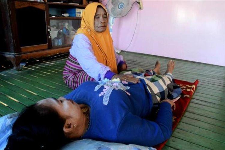 Nenek Wa Musaani, mengurut seorang warga. dari hasil urut ii ia menabung sebagian uangnya untuk berangkat haji.