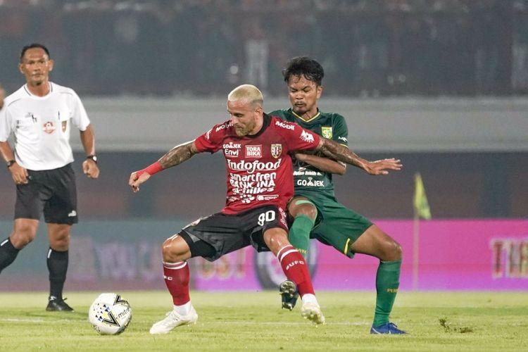 Gelandang bertahan Persebaya Muhammad Hidayat berusaha menghentikan aksi pemain Bali United Paulo Sergio Moreira Goncalves. Persebaya takluk 1-2 pada laga perdana Liga 1 2019 melawan Bali United di Stadion Kapten I Wayan Dipta, Kamis (16/5/2019) malam.