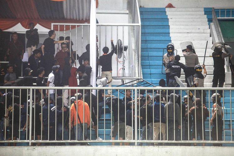 Polisi menghalau pendukung yang ricuh saat pertandingan Liga 1 antara PSS Sleman melawan Arema FC di Stadion Maguwoharjo, Sleman, DI Yogyakarta, Kamis (15/5/2019). Laga pembuka Liga 1 yang diwarnai kericuhan dan sempat dihentikan sementara itu berakhir dengan kemenangan PSS Sleman dengan skor 3-1.