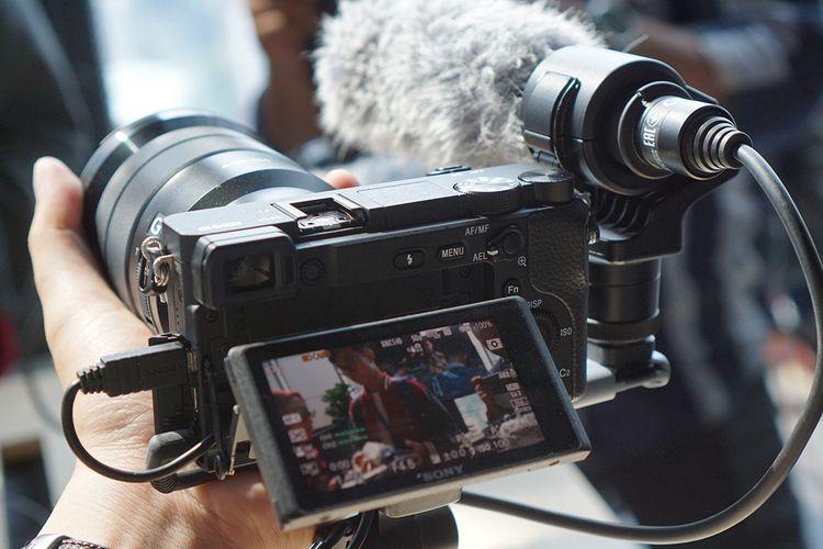 Bagian belakang kamera mirrorless Sony Alpha a6400 dengan aksesori shooting grip GP-VPT1, plate tambahan, mikrofon shotgun. serta lensa SEL 18-105mm F4 dengan zoom elektronik.