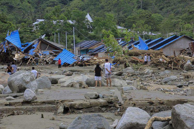 Sejumlah warga melihat rumah yang rusak akibat banjir bandang di Sentani, Kabupaten Jayapura, Papua, Minggu (17/3/2019). Jumlah korban bencana banjir bandang yang terjadi pada Sabtu (16/3/2019) malam kemarin, hingga data yang masuk pada Minggu sore, terus bertambah menjadi 63 orang.
