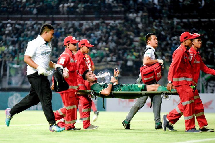 Otavio Dutra harus ditandu keluar saat laga Persebaya vs Persela di Stadion Gelora Bung Tomo, Sabtu (11/5/2019), lantaran bek asal Brazil itu mengalami fracture tulang hidung