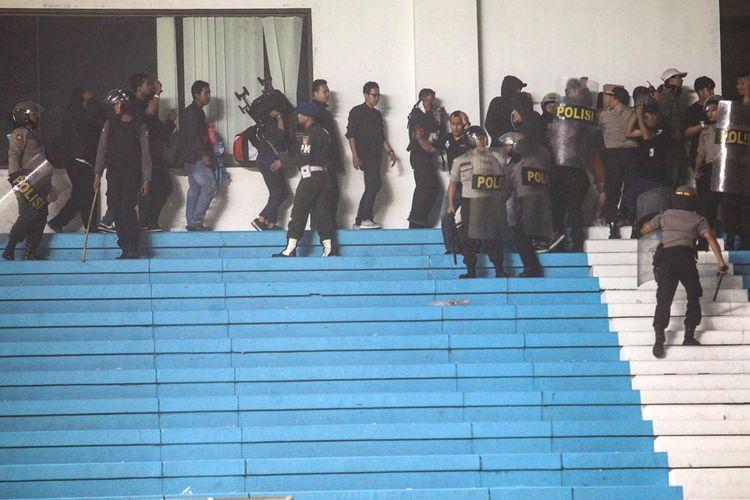 Polisi mengamankan penonton saat terjadi kericuhan  pendukung saat pertandingan perdana Liga 1 antara PSS Sleman melawan Arema FC  di Stadion Maguwoharjo, Sleman, DI Yogyakarta, Kamis (15/5/2019). Laga pembuka Liga 1 yang diwarnai kericuhan dan sempat dihentikan sementara itu berakhir dengan kemenangan PSS Sleman dengan skor 3-1.