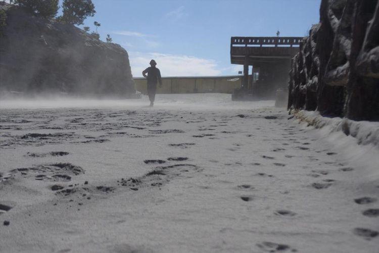 Seorang warga tampak berjalan di atas jalan yang dipenuhi debu vulkanik setebal kurang lebih 5 centimeter di Kawah Ratu, pusat wisata Gunung Tangkuban Parahu, pasca erupsi, Jumat (26/7/2019) kemarin.