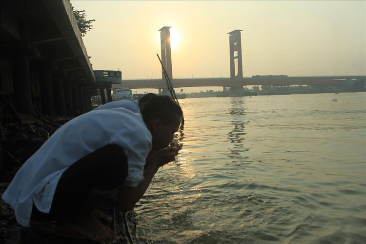 Seorang warga sedang mengambil wudhu di sungai Musi Palembang, untuk melaksanakan shalat Idul Adha di Masjid Sultan Mahmud Badaruddin, Sabtu (11/8/2019). Tampak Jembatan Ampera di kejauhan.