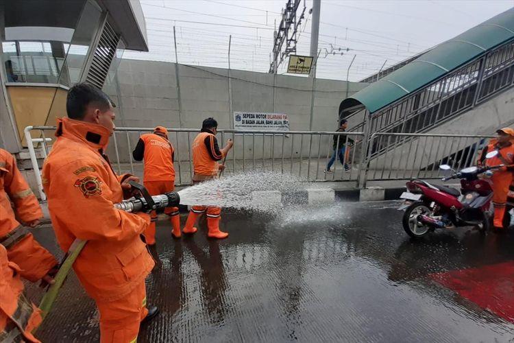 Sejumlah petugas Damkar dan Petugas Dishub DKI sirami jalan di Stasiun MRT Lebak Bulus, Jakarta Selatan karena warga keluhkan bau pesing, Kamis (15/8/2019)