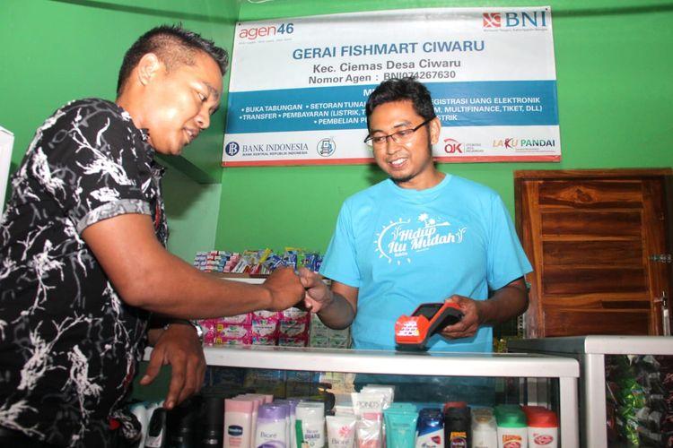 Seorang warga sedang bertransaksi di Agen46 yang juga merupakan Gerai Fish Mart di di Desa Ciwaru, Kecamatan Ciemas, Kabupaten Sukabumi, Jawa Barat, Sabtu (20 Juli 2019). Selain meningkatkan literasi keuangan dan memberikan bantuan CSR berupa mobil ambulans dan Kapal Latih Nelayan berukuran 5 GT di daerah tersebut, BNI juga menyalurkan Kredit Usaha Rakyat (KUR) kepada nelayan yang secara total telah disalurkan sebesar Rp 9,37 triliun kepada 109.020 penerima per 30 Juni 2019.