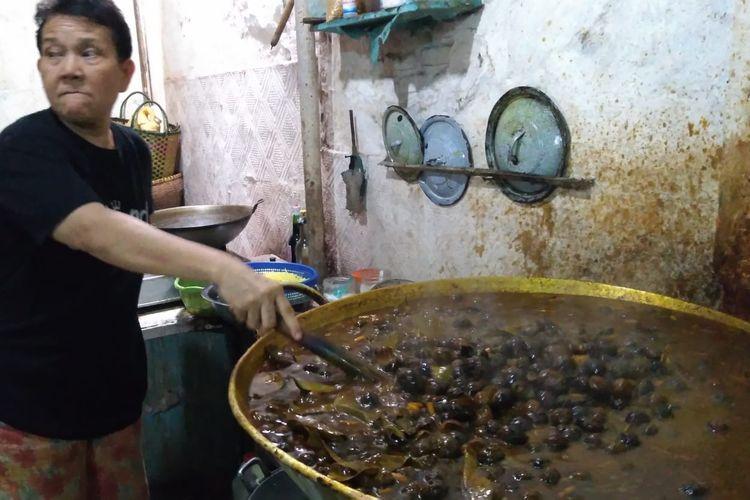Lani memasak keong di rumah sekaligus warung Jalan Kauman Lama, Purwokerto, Jawa Tengah, Sabtu (11/5/2019)
