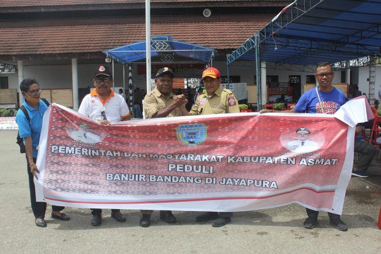 Kepala Dinas Sosial Asmat Amir Mahmud menyerahkan bantuan korban banjir bandang kepada Bupati Jayapura Mathias Awaitouw, di Posko Induk Gunung Merah, Kantor Bupati Jayapura, Minggu (31/3/2019)