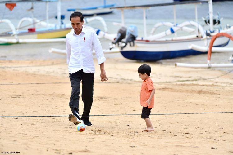 Presiden Joko Widodo bermain bola bersama cucunya, Jan Ethes, di Pantai Sanur Bali, tepatnya di belakang hotel tempatnya dan keluarga menginap, Jumat (14/6/2019), dalam kunjungan kerja ke Provinsi Bali.