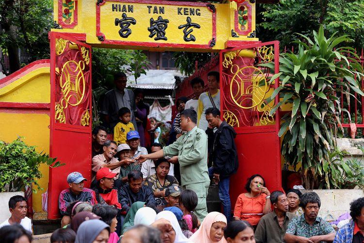 Petugas saat membagikan duit kepada pengemis di Kelenteng Kim Tek Ie atau Vihara Dharma Bakti, Glodok, kawasan Petak Sembilan, Jakarta Barat, Sabtu (28/1/2017). Warga keturunan Tionghoa melakukan sembahyang sebagai ungkapan syukur merayakan Tahun Baru Imlek 2568 dengan Shio pada imlek tahun ini adalah Ayam Api.