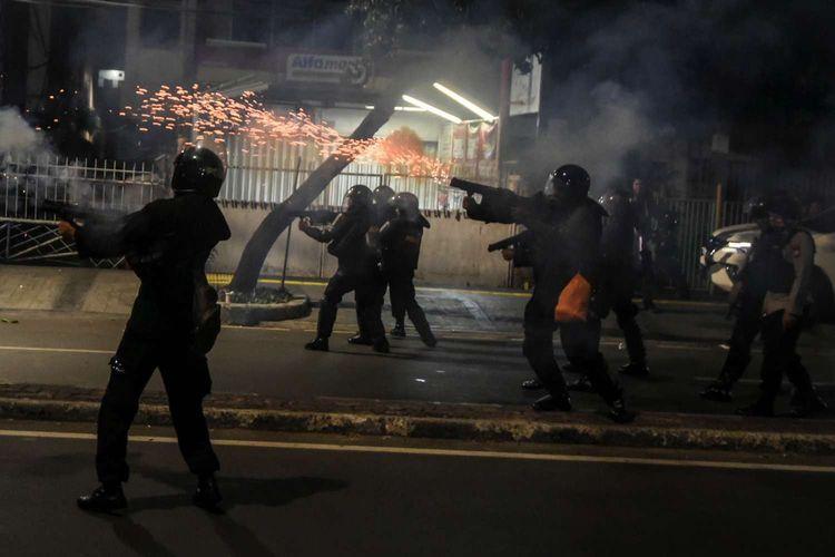 Petugas menembakan gas air mata saat membubarkan massa yang masih bertahan di depan kantor Bawaslu di kawasan Thamrin, Jakarta, Selasa (21/5/2019).