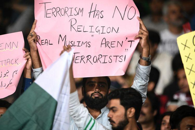 Suporter kriket di Pakistan mengangkat poster menolak tuduhan Muslim sebagai pelaku kekerasan yang menjadi salah satu dalih teroris menyerang dua masjid di Selandia Baru pada Jumat (15/3/2019).