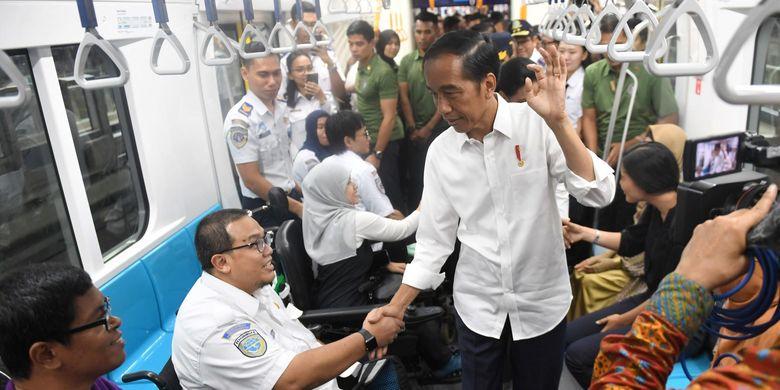 Presiden Joko Widodo (Jokowi) bersalaman dengan penyandang disabilitas saat mencoba menggunakan moda transportasi MRT, di Jakarta.