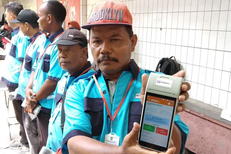 Petugas parkir Koridor Ngapeman Jalan Honggowongso, Joko Waluyo menunjukkan alat parkir elektronik dalam soft launching di Solo, Jawa Tengah, Kamis (9/5/2019).