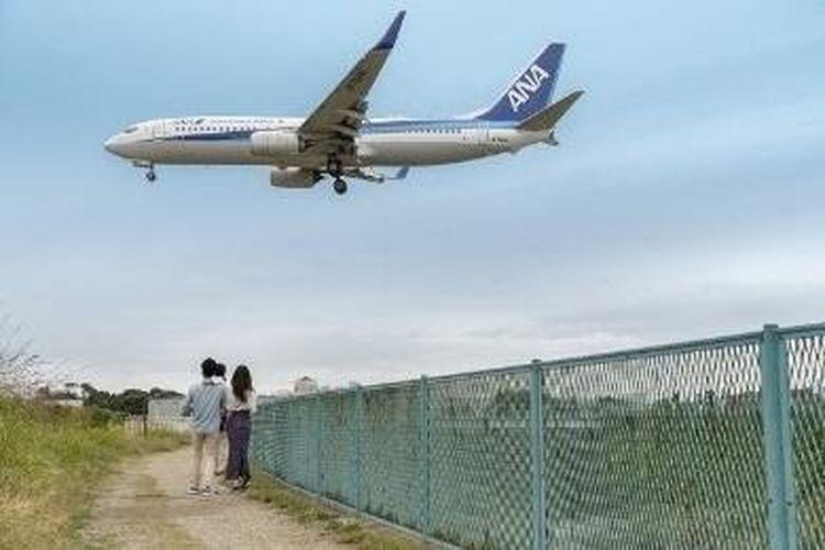 Pesawat terbang melintas hanya beberapa meter di atas kepala. Baling-baling pesawat menghamburkan pasir di tanah.