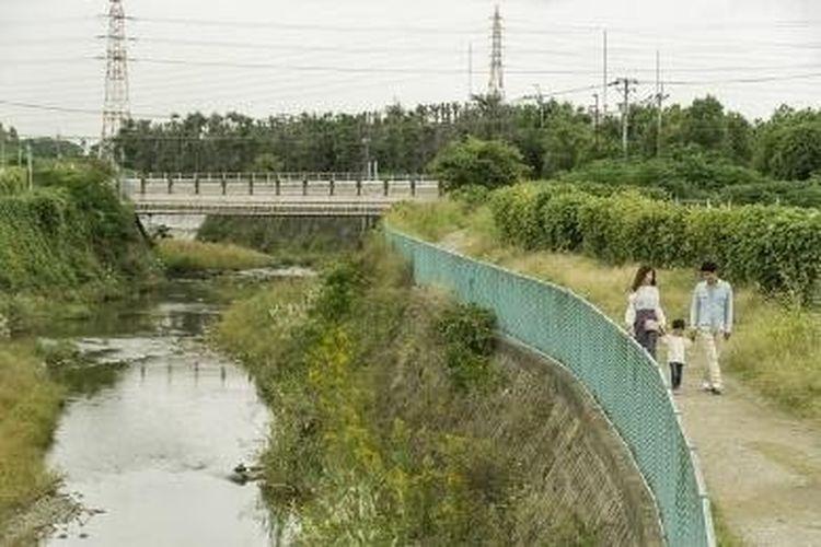 Setelah memarkir mobil, keluarga Sasaki berjalan selama lima menit menuju pinggi Sungai Senri.