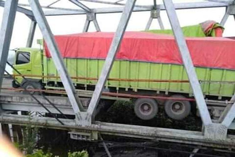 Jembatan Mesuji yang amblas akibat roda sebuah kendaraan truk besar penuh muatan terperosok di bagian tengah jembatan yang aspalnya lepas Minggu (16/6/2019)