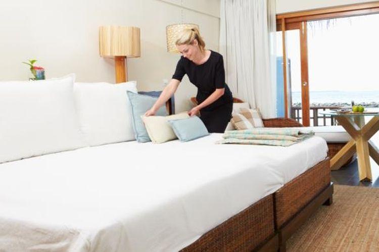 ILUSTRASI - Petugas hotel sedang merapikan kamar tamu.