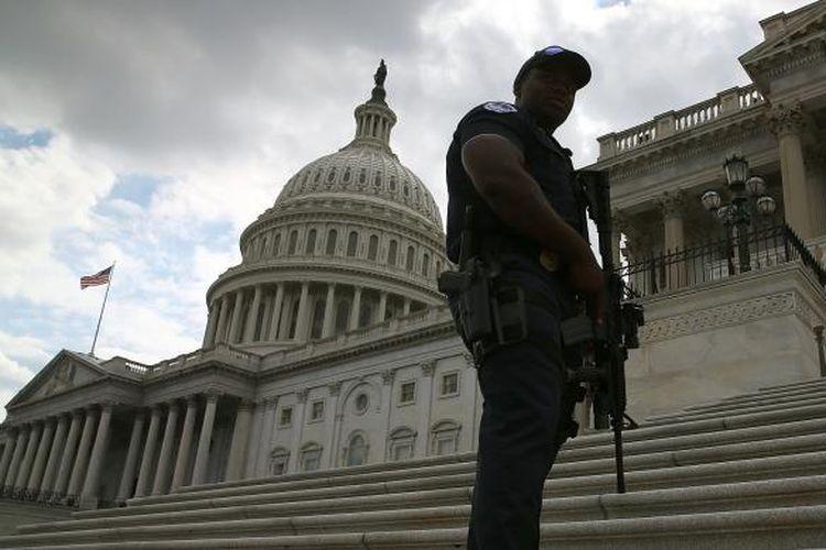 Seorang polisi terlihat bersenjata lengkap mengamankan gedung Capitol di Capitol Hill, Washington, Amerika Serikat, Senin (16/9/2013), menyusul penembakan di pangkalan Angkatan Laut Amerika Serikat yang berjarak kurang dari 3 kilometer dari gedung Senat Amerika ini.